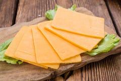 Some Cheddar Slices. (close-up shot) on vintage wooden background stock photo