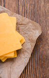 Some Cheddar Slices. (close-up shot) on vintage wooden background Stock Photography