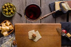 Some cheese and wine set. Palette of many types of cheese and some grapes, olives and wine with copy space royalty free stock images