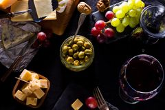 Some cheese and wine set. Palette of many types of cheese and some grapes, olives and wine royalty free stock photo