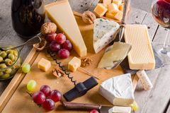Some cheese and wine set. Palette of many types of cheese and some grapes, olives and wine royalty free stock photos