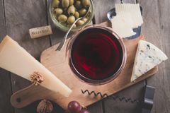 Some cheese and wine set. Palette of many types of cheese and some grapes, olives and wine stock photo