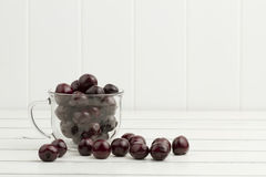 Some cherries in a glass cup. On a white wooden table Stock Photo