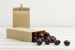 Some cherries in paper bags. White woden background Stock Image