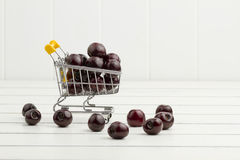 Some cherries in a shopping cart. White wooden background Royalty Free Stock Image