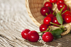 Some Cherries in a small Basket. Some ripe Cherries with sparkling Water Drops in small Basket on a old Wooden Table stock image