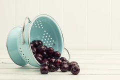 Some cherries in a turquoise strainer. White background Royalty Free Stock Photo