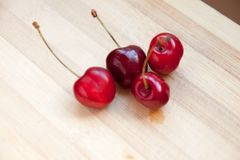 The Four cherries on table. Some cherries on wooden table made with bamboo royalty free stock image
