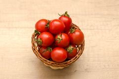 Cherry tomatoes in a basket on a wooden background. Some Cherry tomatoes in a basket on a wooden background Stock Photos