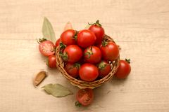 Cherry tomatoes in a basket on a wooden background. Some Cherry tomatoes in a basket on a wooden background Stock Photo
