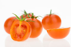 Some cherry tomatoes, one cut in half, on white Royalty Free Stock Photo