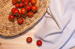 Some cherry tomatoes in a wicked basket and a linen tablecloth o. Cherry tomatoes in a wicked basket and a linen tablecloth on a wood table for background or Royalty Free Stock Photo