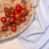Some cherry tomatoes in a wicked basket and a linen tablecloth o. Cherry tomatoes in a wicked basket and a linen tablecloth on a wood table for background or Royalty Free Stock Photography