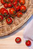Some cherry tomatoes in a wicked basket and a linen tablecloth o. Cherry tomatoes in a wicked basket and a linen tablecloth on a wood table for background or Stock Image