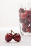 Some cherrys in a glass. On table stock image