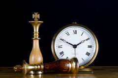 Chessmen with Old Watch. Some Chessmen with a Old Watch. White King with Black King Defeated Royalty Free Stock Images