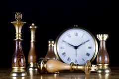 Chessmen with Old Watch. Some Chessmen with a Old Watch. White King Defeated Royalty Free Stock Image
