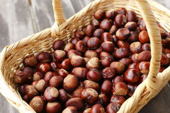 Some chestnuts. In a basket on a wooden plate Royalty Free Stock Photo