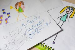 Some children`s drawings and calculations. Some elementary school child`s drawings and simple calculations on white paper Royalty Free Stock Images
