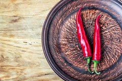 Some chili peppers on dark plate, fresh red ripe hot chilli on old wood board background with copy space, guinea pepper or bird pe. Pper, small capsicum, fiery Royalty Free Stock Photos