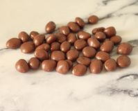 Some chocolate balls. On marble background royalty free stock photo