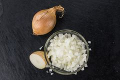 Some Chopped white onions on a dark slate slab. Some White Onions dices on a slate slab as detailed close-up shot; selective focus Royalty Free Stock Photo