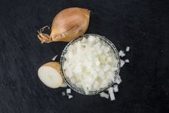 Some chopped white onions on a dark slate slab. Some white onions dices on a slate slab as detailed close-up shot; selective focus Stock Image