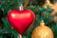 Some christmas baubles. Golden and red bauble decorating a Christmas tree Stock Image