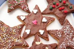 Christmas cookies with chocolate. Some christmas cookies with chocolate and sprinkles of sugar royalty free stock photos