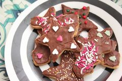 Christmas cookies with sprinkles. Some christmas cookies with chocolate and sprinkles of sugar stock photos