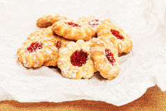 Some christmas cookies with jam. Pile of some christmas cookies with jam on a parchment paper stock image