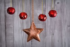 Some Christmas decoration. Close up of Christmas star and red balls hanging on the rope against wooden background Stock Images