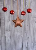 Some Christmas decoration. Close up of Christmas star and red balls hanging on the rope against wooden background royalty free stock photos