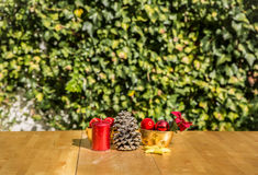 Some Christmas ornaments on a table. In front of a green background Royalty Free Stock Images