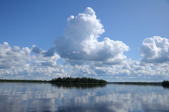 Some clouds above the mirrored lake. The picture shows typical landscape in the south region of Karelia - blue sky, clouds, big lake looks like a mirror and a Stock Photography