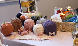 Some coil woolen threads and some hats on a exhibition of objects crocheted Royalty Free Stock Image