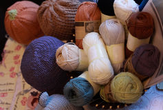 Some coil woolen threads and some hats. Exhibition of objects crocheted Royalty Free Stock Image