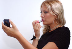 Some color will do!. Young woman doing her makeup Royalty Free Stock Photography