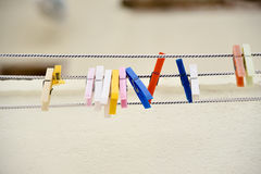 Some colored clothespins. Colored clothespins on a rope Royalty Free Stock Images