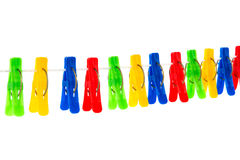 Some colored clothespins on a White background. Colored red, yellow, green, blue clothespins hanging on a rope isolated on white background Royalty Free Stock Images
