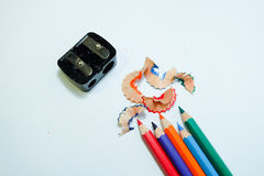 Some colored pencils of different colors and a pencil sharpener and a pencil shaving on white paper background.  Royalty Free Stock Photography