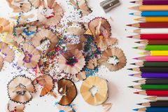 Some colored pencils of different colors and a pencil sharpener and pencil shavings on a white background.  stock image