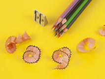 Some colored pencils of different colors and a pencil sharpener. And pencil shavings on the yellow Stock Photos