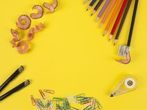 Some colored pencils of different colors and a pencil sharpener. And pencil shavings on the yellow Stock Photo