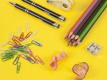Some colored pencils of different colors and a pencil sharpener. And pencil shavings on the yellow Royalty Free Stock Photo