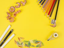Some colored pencils of different colors and a pencil sharpener. And pencil shavings on the yellow Stock Images