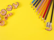 Some colored pencils of different colors and a pencil sharpener. And pencil shavings on the yellow Stock Image