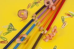 Some colored pencils of different colors and a pencil sharpener. And pencil shavings on the yellow Stock Photography