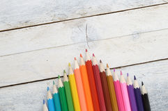 Some colored pencils on a white wooden table. Empty copy space for editor's text Royalty Free Stock Photos