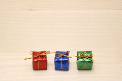 Some colorful gift boxes with gold ribbons. Some colorful gift boxes with gold ribbons on wood Royalty Free Stock Photography